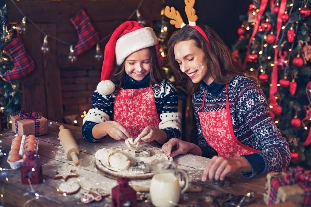 Feliz navidad y felices fiestas, madre e hija cocinando galletas de navidad. Foto Premium